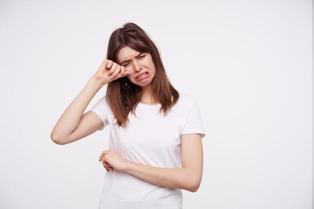 Ongelukkige jonge donkerharige vrouw gekleed in een wit basic t-shirt houdt haar ogen gesloten terwijl ze huilt en veegt de tranen van haar gezicht, geïsoleerd over witte muur