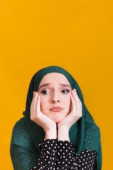 Ongelukkige jonge islamitische vrouw die weg voor gele achtergrond kijken