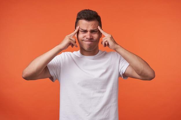 Ongelukkige jonge knappe bruinharige man met kort kapsel vingers houden op de slapen en fronsend gezicht terwijl staande over de oranje achtergrond in wit basic t-shirt