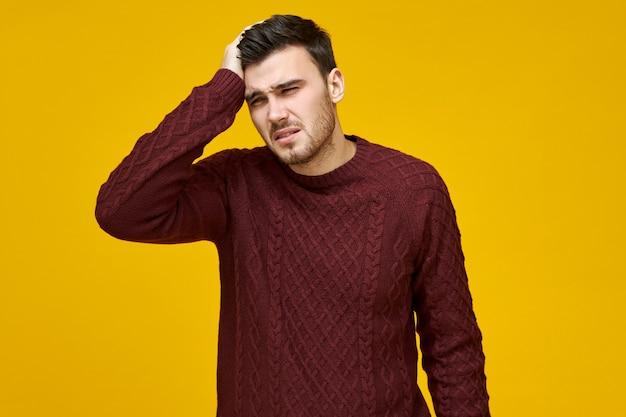 Ongelukkige jonge man in warme trui met verkoudheid, griep of een slechte dag op het werk lijdt aan splijtende hoofdpijn, hand vasthouden zoon zijn hoofd, heeft medicijnen tegen koorts nodig om de temperatuur te verlagen