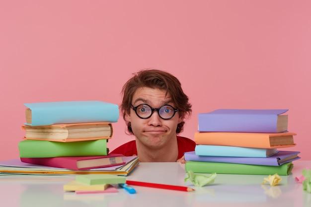 Ongelukkige jonge man met bril draagt in rood t-shirt, verstopt aan de tafel met boeken, geïsoleerd op roze achtergrond. ziet er ontevreden en verdrietig uit.