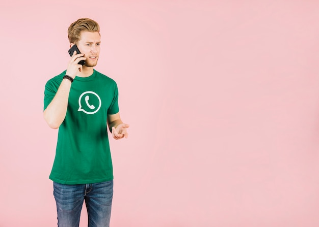 Ongelukkige jonge mens die op cellphone tegen roze achtergrond spreekt