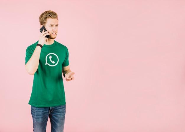 Ongelukkige jonge mens die op mobiele telefoon tegen roze achtergrond spreekt