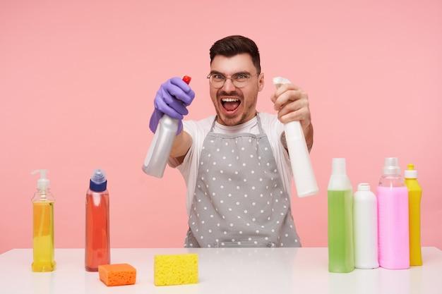 Ongelukkige jonge mooie brunette man met kort kapsel kijkt vreugdevol terwijl hij zijn handen opheft met huishoudelijke chemicaliën, plezier maakt tijdens het schoonmaken van huis, geïsoleerd op roze