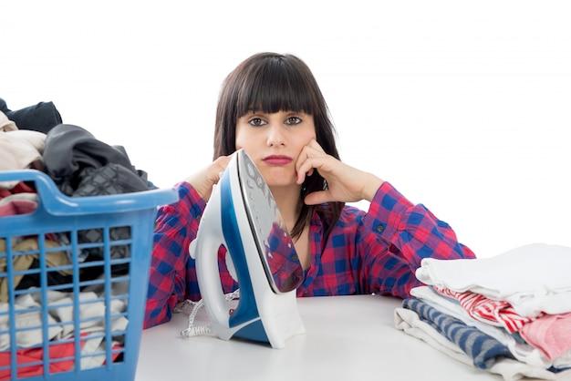 Ongelukkige jonge mooie vrouw strijken van kleding
