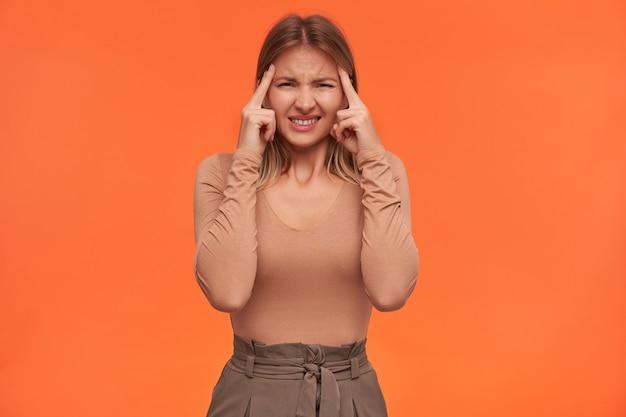 Ongelukkige jonge mooie witharige vrouw met kort kapsel fronst haar gezicht terwijl ze sterke hoofdpijn heeft en haar handen opheft naar haar slapen, poseren over oranje muur