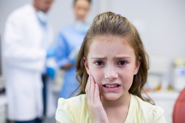 Ongelukkige jonge patiënt met kiespijn in de tandheelkundige kliniek