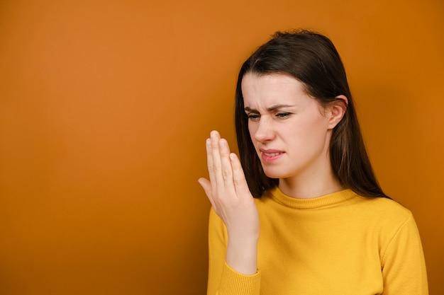 Ongelukkige jonge vrouw die haar adem met hand controleert