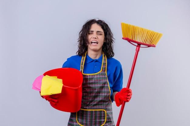 Ongelukkige jonge vrouw die schort en rubberhandschoenen draagt die emmer met het schoonmaken van tol houden en dweilen benadrukt met negatieve emotie gezichtsuitdrukking die zich over witte achtergrond bevindt