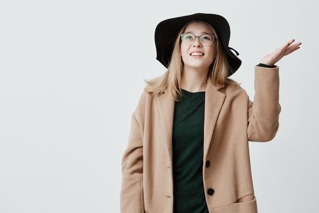 Ongelukkige jonge vrouw fronst haar gezicht van ongenoegen, haalt haar schouders op, heeft een slecht humeur, is van streek vanwege regenachtig weer en controleert of het blijft regenen. studentenmeisje die laag, glazen en hoed dragen
