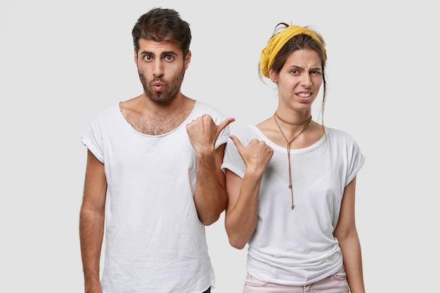 Ongelukkige jonge vrouw met europees uiterlijk, wijst met duim naar verbaasde man, uiting van afkeer en verrassing, draag casual t-shirts, geïsoleerd over witte muur
