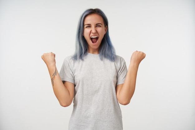 Ongelukkige jonge vrouw met kort blauw haar emotioneel opheffen van haar handen en gelukkig schreeuwen met brede mond geopend, geïsoleerd op wit