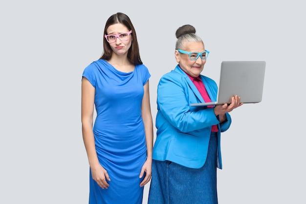 Ongelukkige jonge vrouw staat in de buurt van geluk oudere vrouw werkcomputer