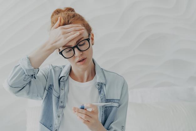 Ongelukkige jonge vrouw verdrietig vanwege onvruchtbaarheid kijkt naar zwangerschapstest met negatief resultaat