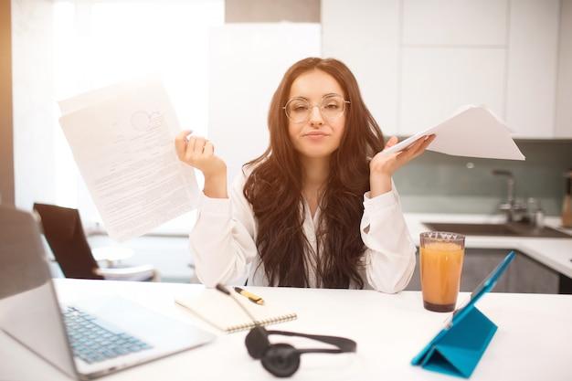 Ongelukkige jonge vrouw werkt de keuken in haar huis, ze is erg moe. maar nog steeds veel werk. thuiswerken is moeilijk en vermoeiend