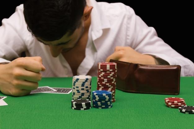 Ongelukkige jongeman die zich verdrietig, wanhopig en gestrest voelt nadat hij zijn geld heeft verloren door poker en blackjack te spelen in een nachtelijk casino. kopieer ruimte
