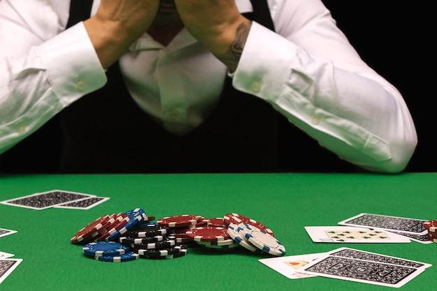 Ongelukkige jongeman die zich verdrietig, wanhopig en gestrest voelt nadat hij zijn geld heeft verloren door poker en blackjack te spelen in een nachtelijk casino.