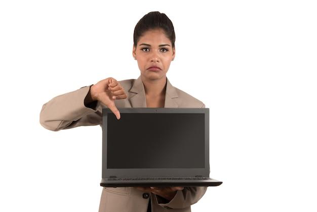 Ongelukkige laptop van de bedrijfsvrouwenholding en het tonen van duimen omlaag geïsoleerd op een witte achtergrond