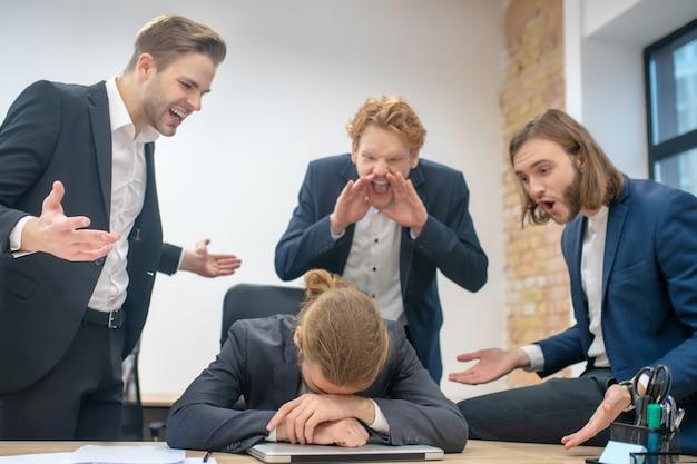 Ongelukkige man aan tafel met zijn hoofd gebogen naar laptop en drie schreeuwende boze collega's in kantoor