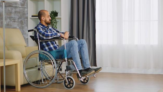 Ongelukkige man in rolstoel in woonkamer kijkend naar raam.