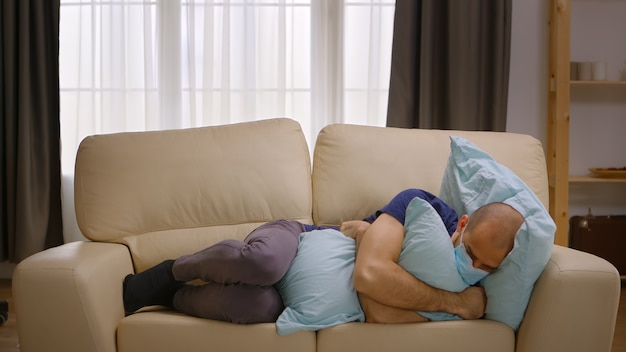 Ongelukkige man met beschermingsmasker die een kussen knuffelt dat op de bank ligt tijdens coronavirusvergrendeling.