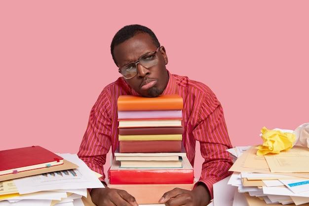 Ongelukkige man met donkere huid in formele kleding, teleurgesteld, moe van het werk, leunt op een stapel boeken, draagt een grote bril en een formeel overhemd