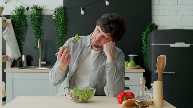 Ongelukkige man plantaardige salade eten aan tafel in de keuken