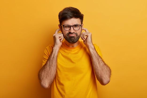 Ongelukkige man stopt oren met vingers om niet meer te horen, negeert luide muziek van buren, voelt zich ongemakkelijk, staat tegen gele muur, wordt gestoord door hinderlijk geluid of lawaai.