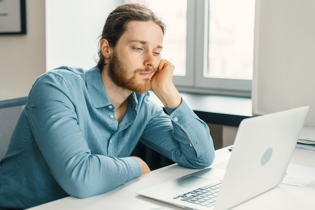 Ongelukkige mannelijke kantoormedewerker die zich verveelt op het werk