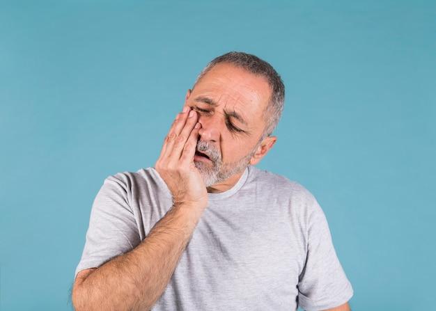 Ongelukkige mens die tandpijn heeft en zijn wang aanraakt