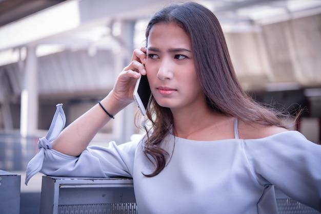 Ongelukkige mooie aziatische vrouw die op telefoon spreekt