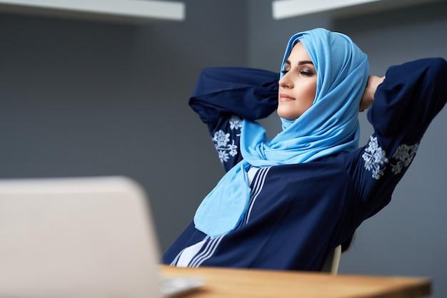Ongelukkige moslim vrouwelijke student die in bibliotheek leert