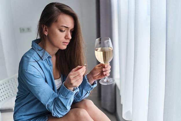 Ongelukkige nadenkend drinkende gescheiden vrouw met wijnglas houdt gouden ring vast tijdens het denken en zich zorgen maken over het einde van het huwelijk na het verbreken van de relatie en echtscheiding