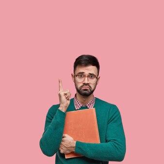 Ongelukkige ontevreden man fronst zijn wenkbrauwen, geeft met wijsvinger boven aan, draagt bril en groene trui, ontevreden over slecht nieuws