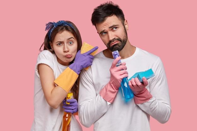 Ongelukkige ontevreden vrouw en man houden spray vast, sponzen, gekleed in witte vrijetijdskleding, betrokken bij het schoonmaken, huishoudelijke klusjes in het weekend