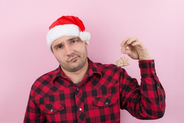 Ongelukkige, overstuur man in een rode hoed heeft een klein geschenk met walging op zijn gezicht