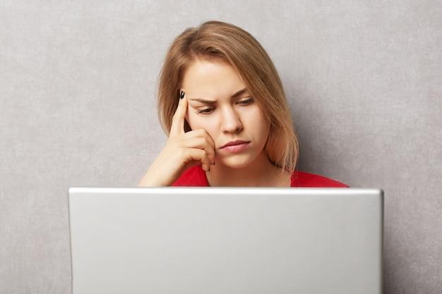 Ongelukkige peinzende ernstige vrouwelijke copywriter concentreerde zich op het schrijven van nieuw artikel