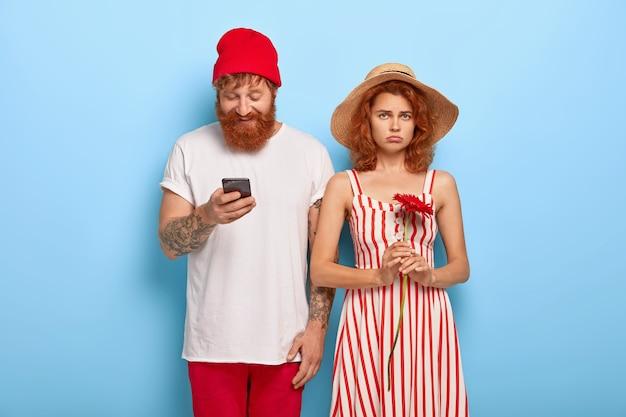 Ongelukkige roodharige vrouw verveelt zich terwijl vriendje een mobiele telefoon gebruikt