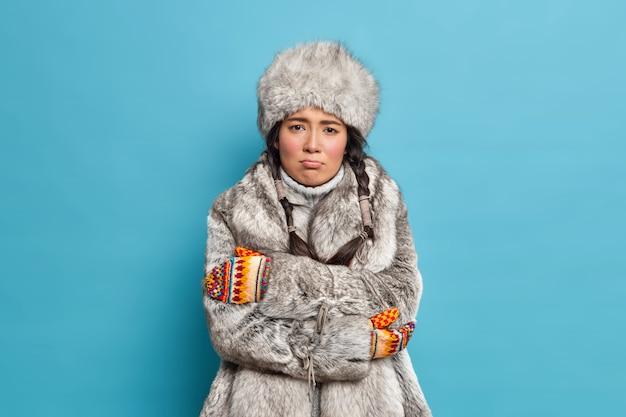 Ongelukkige scandinavische vrouw in bontmuts en jas kruist handen en voelt ijskoud beeft tijdens strenge ijzige dag draagt winter bovenkleding