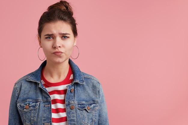 Ongelukkige schattige jonge vrouw in denim jasje gestreept t-shirt, haar gezicht fronsend en camera kijken, geïsoleerd over roze muur. vrouw na te denken over moeilijke situatie in haar leven.