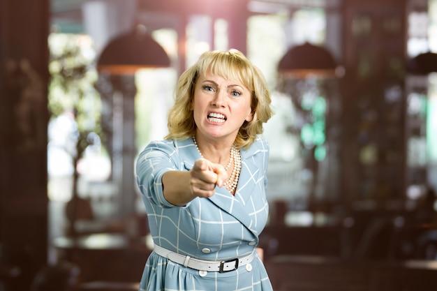Ongelukkige schreeuwende vrouw, wazig. gefrustreerde vrouw van middelbare leeftijd schreeuwen en dreigend met wijsvinger tegen iemand, wazig.