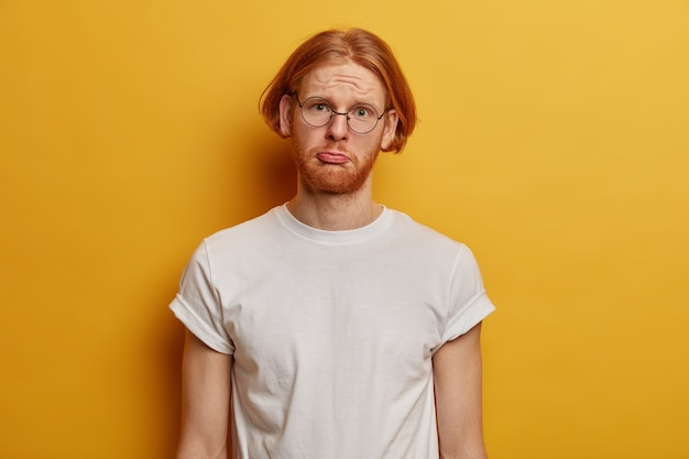 Ongelukkige sombere kerel hipster met gemberhaar, dikke baard, portemonnees onderlip