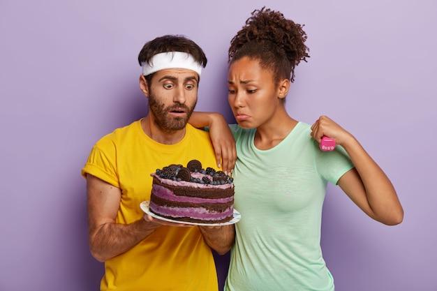 Ongelukkige sportieve diverse jonge vrouw en man kijken met verleiding naar heerlijke cake, wil eten maar beseffen dat het schadelijk is, trainen met halters, gekleed in vrijetijdskleding