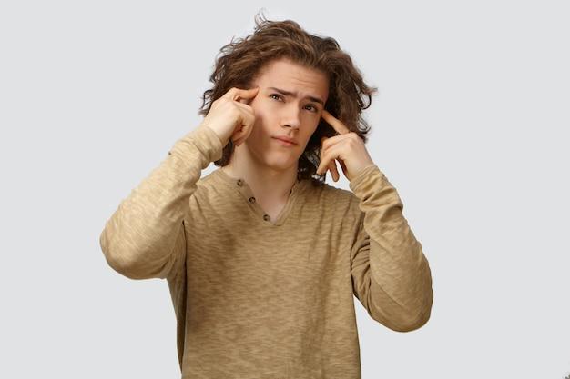 Ongelukkige student met krullend haar die zich overbelast voelt door test of examen, lijdt aan zware hoofdpijn, tempels masseren, pijnlijke gestreste gezichtsuitdrukking heeft, er ellendig en uitgeput uitziet