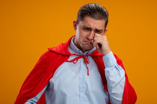 Ongelukkige superheldzakenman in rode cape die wrijvende ogen huilen die zich over oranje muur bevinden