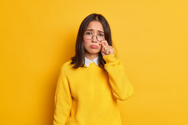 Ongelukkige trieste neerslachtige vrouw met oosterse uitstraling wrijft tranen wil huilen voelt wanhopig heeft problemen in het leven draagt een ronde bril en een losse trui.