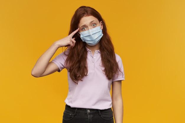 Ongelukkige vermoeide jonge vrouw die een medisch beschermend masker draagt, wijzend op haar tempel over de gele muur