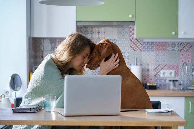 Ongelukkige volwassen vrouw knuffelt hond depressief met nieuwe baan vacatures zoeken zit alleen in de keuken