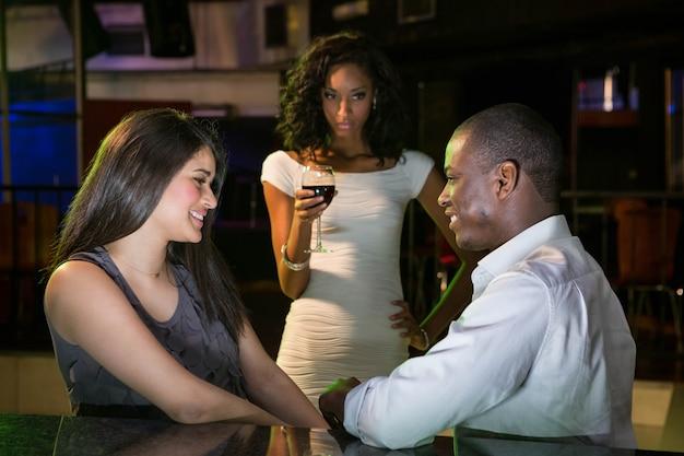 Ongelukkige vrouw die een paar bekijkt die dichtbij barteller flirten in bar