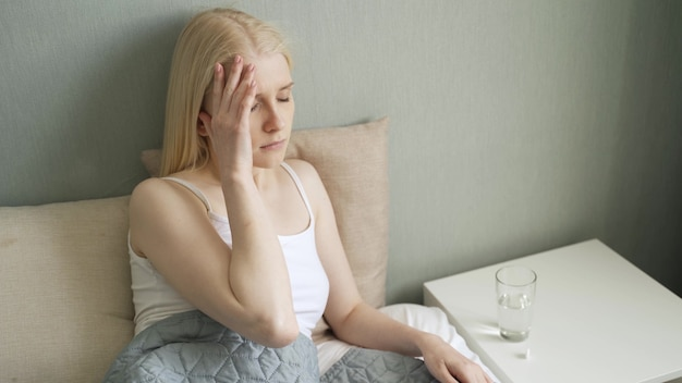 Ongelukkige vrouw die pillen neemt en glas water drinkt, ongezond meisje verdrietig boos gezicht uitdrukkingen die pijnstiller nemen